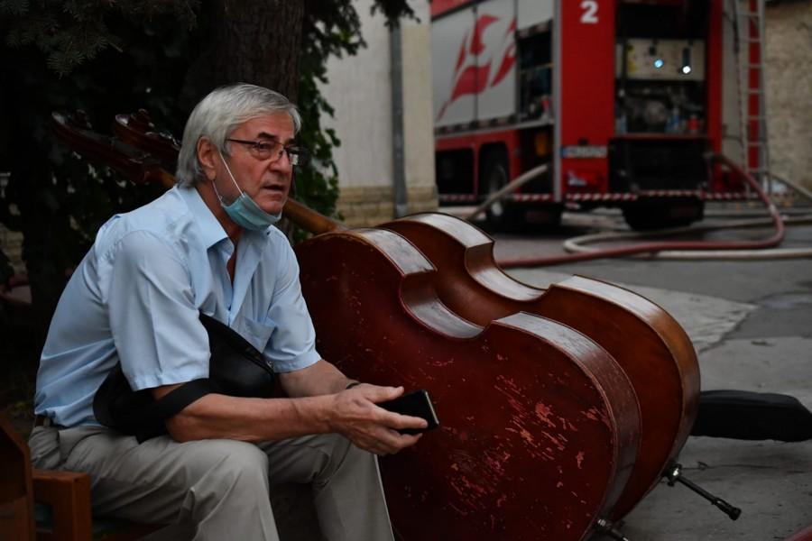 Imaginea neputinței: Dirijorul Petre Neamțu păzind instrumentele salvate din flăcările care au mistuit Filarmonica Națională din Chișinău